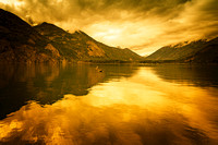 Light it up - a golden/fiery spin on calm Lake Chelan looking towards northern shores from dock at Stehekin.